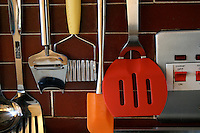 Kitchen utensils hanging beside the cooker