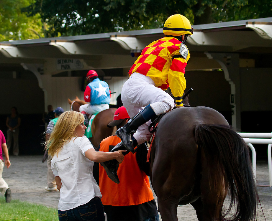 Veteran Jockey Cornelio Velasquez in the paddock being helped aboard by Linda Rice before the ninth race. They won the race. It was Linda's 999th win.