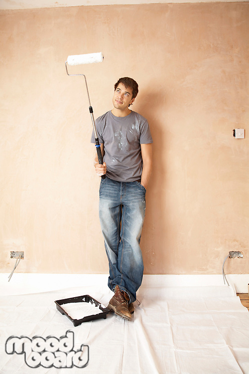 Man standing with paint roller in unrenovated room portrait