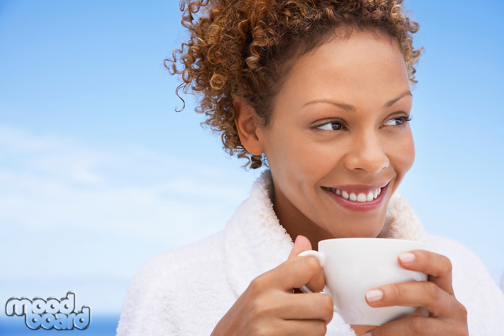 Woman in bathrobe holding up of tea head and shoulders