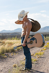 shirtless cowboy on a dirt road with a guitar and a duffel bag on a dirt road