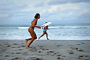 Young women at the beach skimboarding, taking advantage of the final minutes of daylight, in Indialantic, Florida