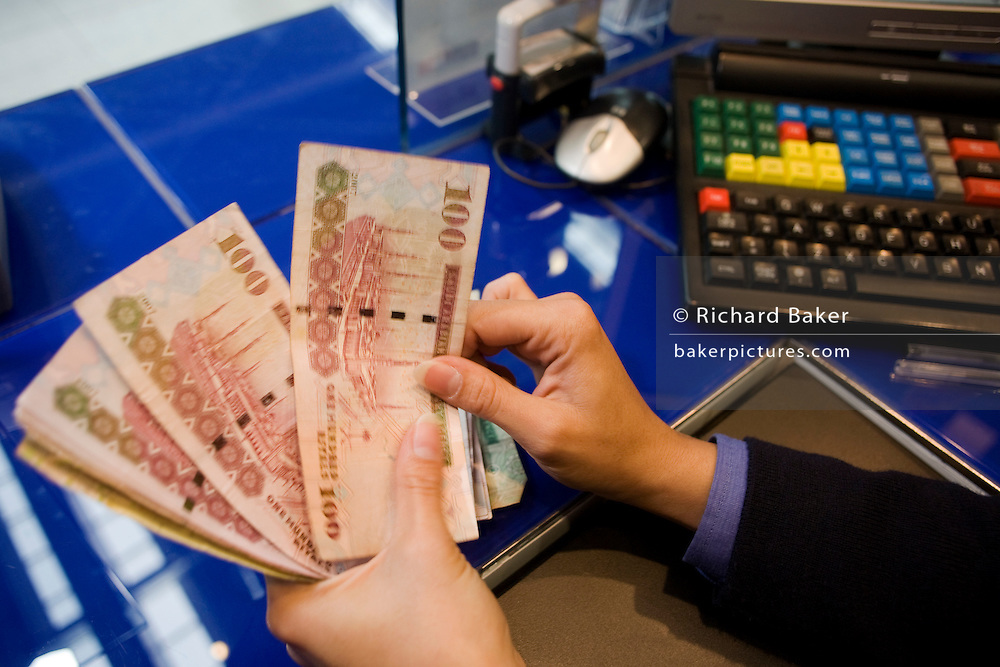 An assistant counts through Suadi Riyal notes at the Travelex bureau de change at Heathrow Airport's Terminal 5.
