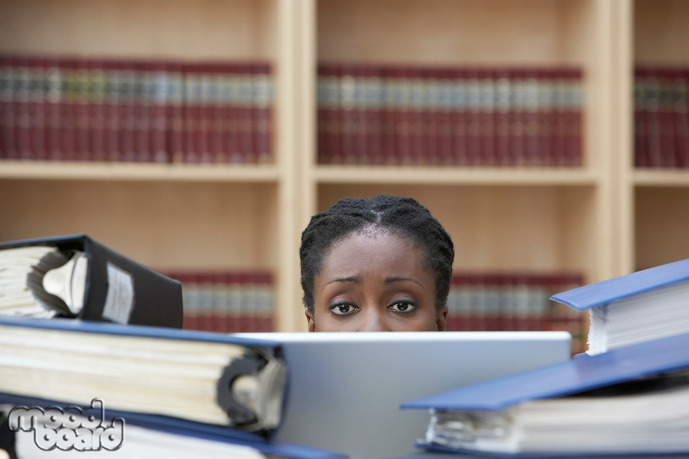 Office worker using laptop sitting behind stacks of documents in office high section