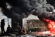 18 MAY 2010 - BANGKOK, THAILAND:  Anti government protesters take cover from snipers as a tire barricade burns at Din Daeng Intersection in Bangkok Tuesday. The intersection has been under periodic sniper fire from unidentified snipers near Thai military lines. Violent unrest continued in Bangkok again Tuesday nearly a week after Thai troops started firing on protesters and Bangkok residents took to the streets in violent protest against the government. Tuesday was not as violent as previous days however. Although protesters continued to set up roadblocks and flaming tire barricades across parts of the city, there was not as much gunfire from the government lines. The most active protesters were at the Din Daeng Intersection about a mile from the Red Shirts' Ratchaprasong camp.  PHOTO BY JACK KURTZ