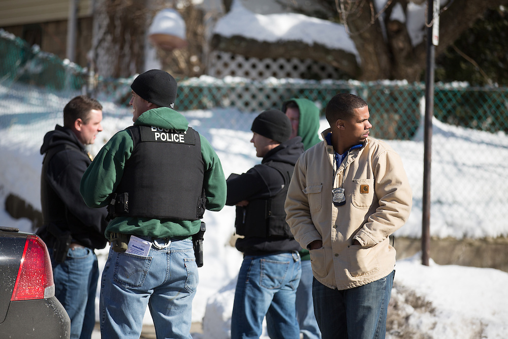 Boston, MA 02/07/2014<br /> Boston Police officers, including officer Diamantino &quot;D&quot; Araujo, at right, secure a house at 650 Walk Hill St in Mattapan where the gun used in Friday's shooting of a 9 year old boy was reportedly recovered.<br /> Alex Jones / www.alexjonesphoto.com
