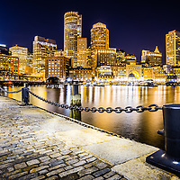 Boston Harbor skyline at night at the Boston Harborwalk waterfront. Includes downtown Boston skyscrapers and Nothern Avenue Bridge.
