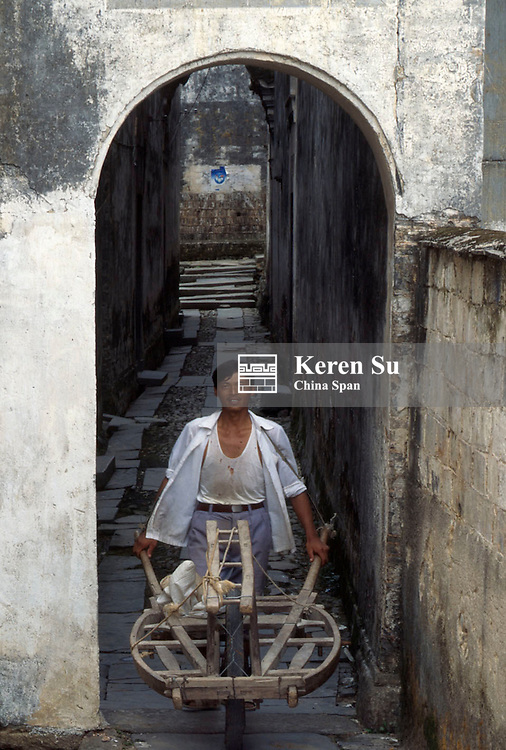 Man pushing a wheelbarrow in an old lane, Anhui Province, China