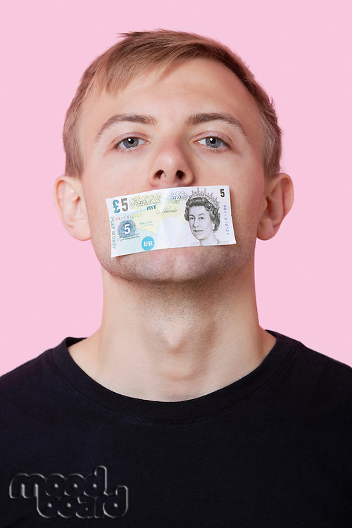 Portrait of a young man with paper money stuck over his mouth against pink background