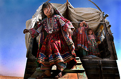 ZHARE DASHT,AFGHANISTAN - SEPT. 4:  Afghan Kuchi nomad children that were living in a camp for displaced people around Spin Boldak, near the border of Pakistan and southern Afghanistan, are relocated to the encamptment of Zhare Dasht by the UNHCR September 4, 2002.  As an estimated 1.6 million Afghan refugees return to Afghanistan,  ethnic Pashtuns from northern Afghanistan are seeking safety in   camps in the south. Numbering up to 120,000,  Pashtuns and Kuchis are fleeing the Tajik- and Uzbek-dominated cities of the north out of fear and prefer to live in the dismal camps like Zhare Dasht which is set in the middle of a desert surrounded by mines about 30 kilometers west of Kandahar. (Photo by Ami Vitale/Getty Images)