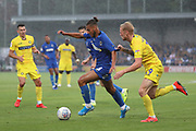 AFC Wimbledon defender Nesta Guinness-Walker (18) dribbling past Wycombe Wanderers defender Jack Grimmer (19) who is pulling his shirt during the EFL Sky Bet League 1 match between AFC Wimbledon and Wycombe Wanderers at the Cherry Red Records Stadium, Kingston, England on 31 August 2019.
