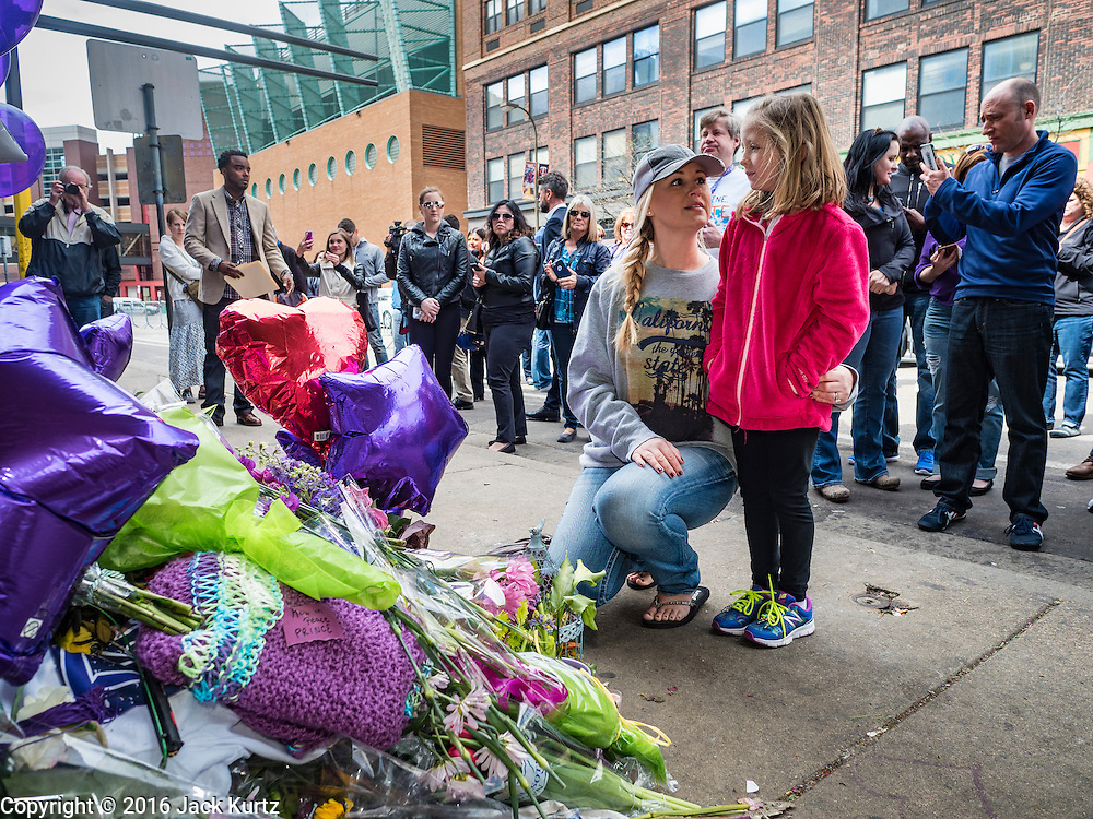 "22 APRIL 2016 - MINNEAPOLIS, MN: A woman and her daughter look at a memorial for Prince at 1st Ave in Minneapolis. Thousands of people came to 1st Ave in Minneapolis Friday to mourn the death of Prince, whose full name is Prince Rogers Nelson. 1st Ave is the nightclub the musical icon made famous in his semi autobiographical movie ""Purple Rain."" Prince, 57 years old, died Thursday, April 21, 2016, at Paisley Park, his home, office and recording complex in Chanhassen, MN.    PHOTO BY JACK KURTZ"