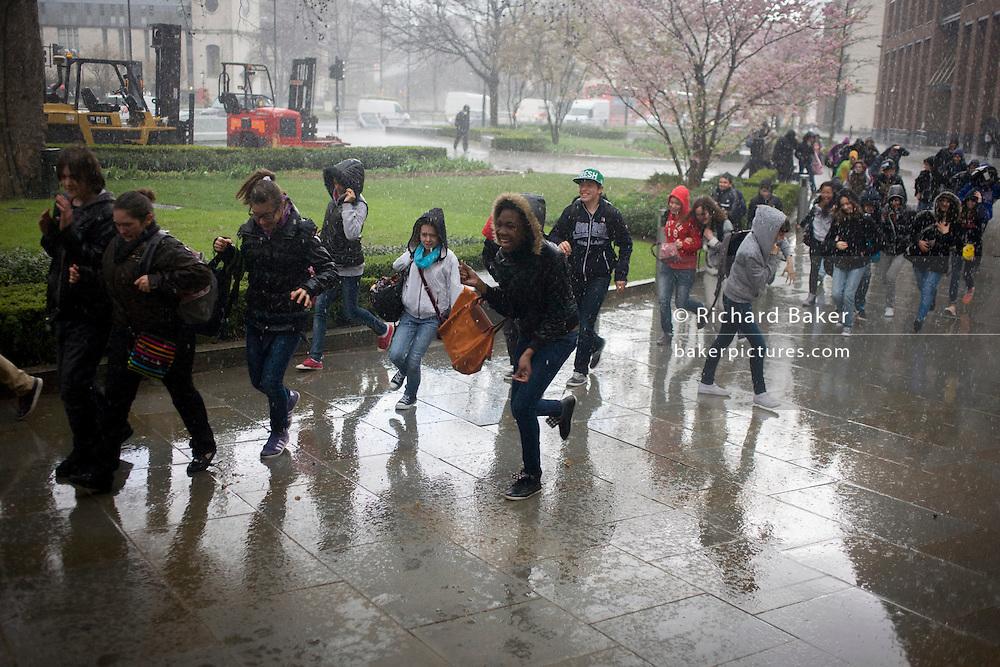 Schoolchildren enjoy dashing through a London street during a brief but intense rain shower.