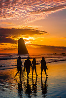 People in silhouette walking on the beach at sunset with The Needles in background, Cannon Beach, Oregon USA.