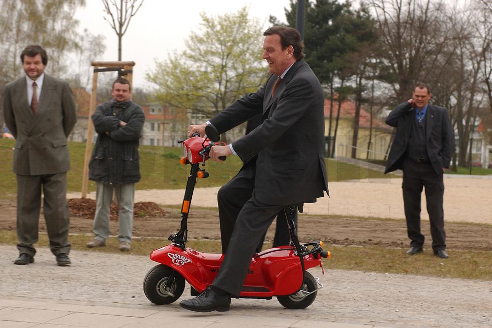 """11 APR 2002, MAGDEBURG/GERMANY:<br /> Gerhard Schroeder, SPD, Bundeskanzler, faehrt auf einem in der FH entworfenen Elektroroller """"Charlie"""" der MZ Motorradwerke, Besuch der Fachschule Magdeburg-Stendal<br /> IMAGE: 20020411-01-029<br /> KEYWORDS: Gerhard Schröder, Motorroller, Roller"""