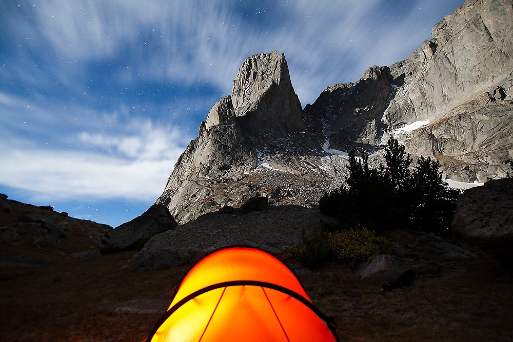 Moonlight illuminates War Bonnet Peak above a glowing tent in the Cirque of the Towers, Popo Agie Wilderness, Wind River Range, Wyoming.