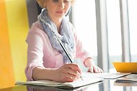 Mid adult businesswoman writing on notepad at desk in office
