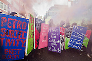 A group of hooded students with anarchist flags carry placard shields and hold smoke flares as they are watched from the Home Office - A student march against fees and many other issues starts in Malet Street and heads for Westminster via the West End.