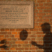"The shadows of pupils passing a ball is cast on a plaque dedicated to William Web Ellis as they pose for another photographer at Rugby school in central England, January 20, 2015.  The public school, founded in 1567 was amongst the first ""Public"" schools in England. The school is known as the home of rugby. Local legend  states that in 1823 pupil William Webb Ellis first ran with the ball inventing the game of rugby football which took its name from the school. In 2015 20 countries will compete in the Rugby World Cup which is hosted by England REUTERS/Neil Hall"