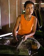 Mentawai Indigenous woman grinding sago (Indonesia).