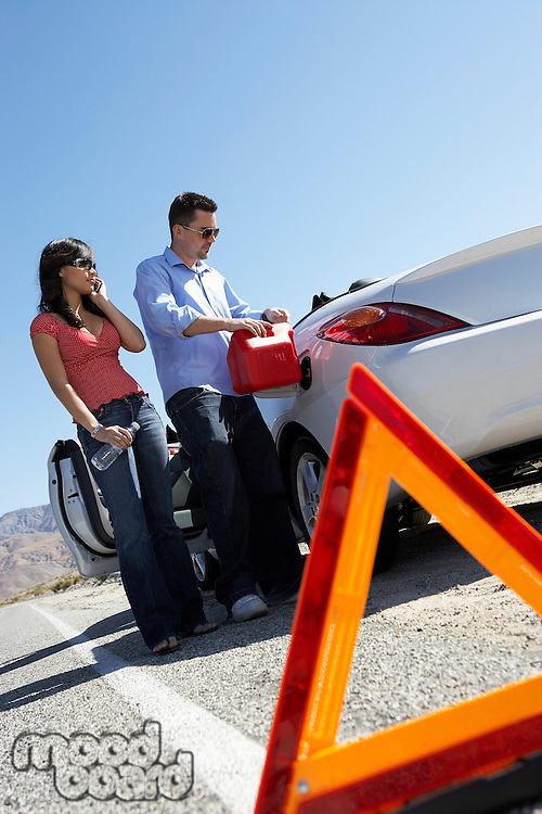 Warning triangle in front of couple pouring fuel into car on desert road