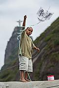A young Brazilian boy flies a kite in the Favela Santa Marta with the Christ Redeemer statue behind in Rio de Janeiro, Brazil.