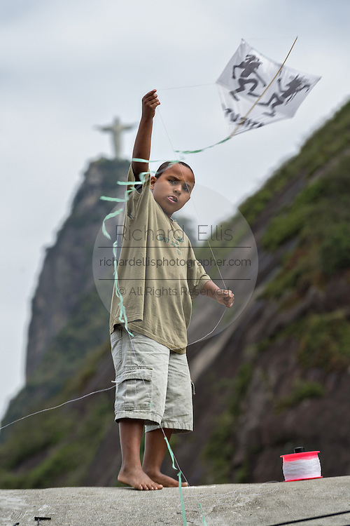 A young Brazilian boy flies a kite in the Favela Santa Marta with the Christ Redeemer statue behind in Rio de Janeiro, Brazil.
