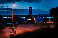 Boy riding a bike home after a village party in Västanvik, Sweden
