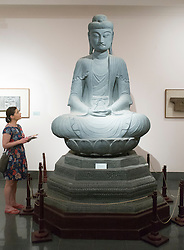 Woman looking at Buddha statue in Vietnam Museum of Fine Arts in Hanoi