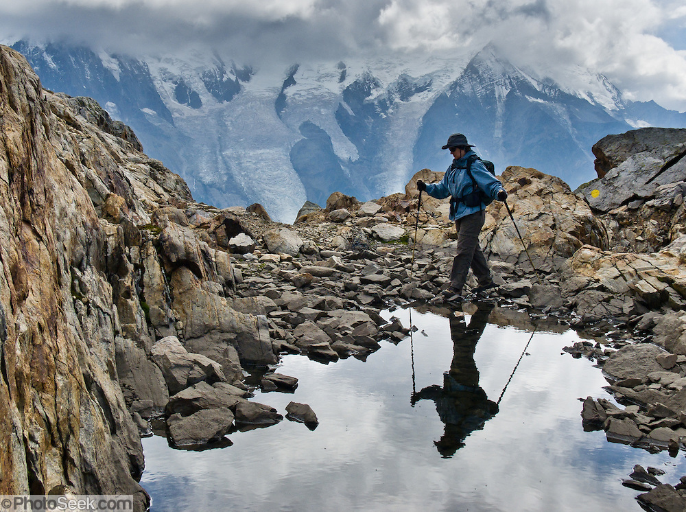 Carol treks the High Route (Chamonix-Zermatt Haute Route) across from vast glaciers of the Mont Blanc Massif, Chamonix, France, Europe. A mountain pond (tarn) reflects the hiker in the Reserve Naturelle Aiguilles Rouges. For licensing options, please inquire.