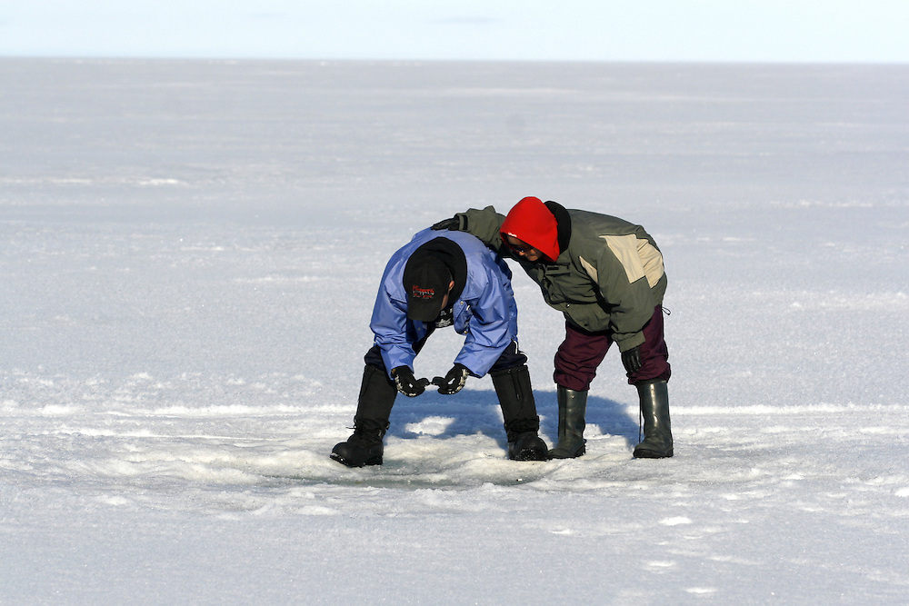 Levi Kalouk and Carol Killittie look down into a Seal breathing hole in the frozen sea of Resolute Bay, northernmost Canada on Tuesday, June 12, 2007..... **GERMANY OUT**