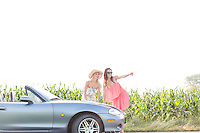Woman showing something to female friend while standing by convertible