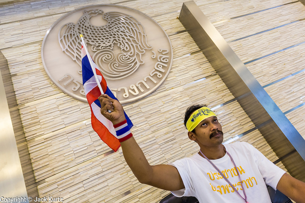 26 NOVEMBER 2013 - BANGKOK, THAILAND:  A Thai anti-government protestor waves a Thai flag in the Ministry of Finance in Bangkok. Protestors opposed to the government of Thai Prime Minister Yingluck Shinawatra spread out through Bangkok this week. Protestors have taken over the Ministry of Finance, Ministry of Sports and Tourism, Ministry of the Interior and other smaller ministries. The protestors are demanding the Prime Minister resign, the Prime Minister said she will not step down. This is the worst political turmoil in Thailand since 2010 when 90 civilians were killed in an army crackdown against Red Shirt protestors. The Pheu Thai party, supported by the Red Shirts, won the 2011 election and now govern. The protestors demanding the Prime Minister step down are related to the Yellow Shirt protestors that closed airports in Thailand in 2008.    PHOTO BY JACK KURTZ