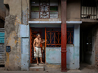Man, looking to his left, at the entrance to a building in Havana.