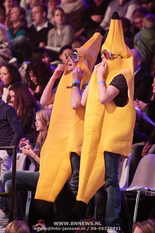 NLD/Hilversum/20110304 - Sterren Dansen op het IJs show 6, Broers van Ralph Mackenbach verkleed als banaan op de tribune