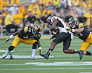 August 31 2013: Northern Illinois Huskies wide receiver Aregeros Turner (14) is brought down by Iowa Hawkeyes defensive back Desmond King (14) and Iowa Hawkeyes defensive back John Lowdermilk (37) during the second half of the NCAA football game between the Northern Illinois Huskies and the Iowa Hawkeyes at Kinnick Stadium in Iowa City, Iowa on August 31, 2013. Northern Illinois defeated Iowa 30-27.