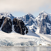A scenic view of steep snow-covered rocky mountains as seen from Petermann Island in Antarctica.