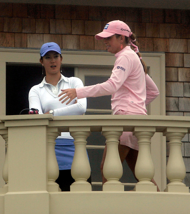 Michelle Wie (L) of the US and Paula Creamer (R) of the US talk on the porch of the clubhouse while play is delayed due to fog during the first day of the US Women's Open Golf Championship at Newport Country Club in Newport Rhode Island, Thursday  29 June 2006