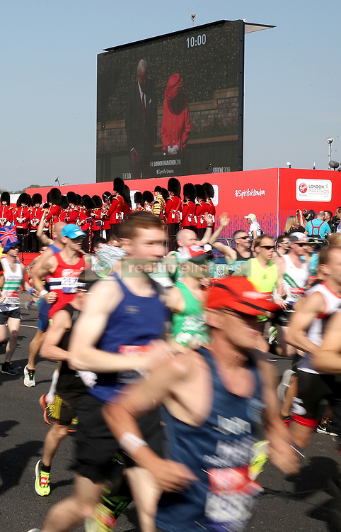Runners make their way past the video screen Queen Elizabeth II after she started the marathon via video link from Windsor Castle during the 2018 Virgin Money London Marathon.