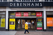 A woman walks past the Folkestone Debenhams store in the final few days of the 'Everything Must Go' sale before closing down in Folkestone, Kent. United Kingdom. The company announced the closure of 19 stores across the UK after going into administration in 2019.  (photo by Andrew Aitchison / In pictures via Getty Images)