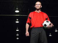 Soccer player holding ball portrait low angle view