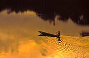 Indigenous person rowing a dugout canoe, rain forest of Ecuador, Rio Napo River.