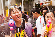14 APRIL 2013 - BANGKOK, THAILAND:  Women take part in a community fight on Silom Road on April 14, 2013 in Bangkok, Thailand. The Songkran festival is celebrated in Thailand as the traditional New Year's Day from 13 to 15 April. The throwing of water originated as a way to pay respect to people and is meant as a symbol of washing all of the bad away. PHOTO BY JACK KURTZ