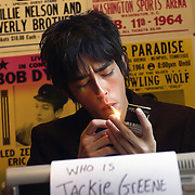 Musician Jackie Greene lights up a cigarette at the typewriter used to write lyrics for his songs. He is inspired by posters of his musical heroes.