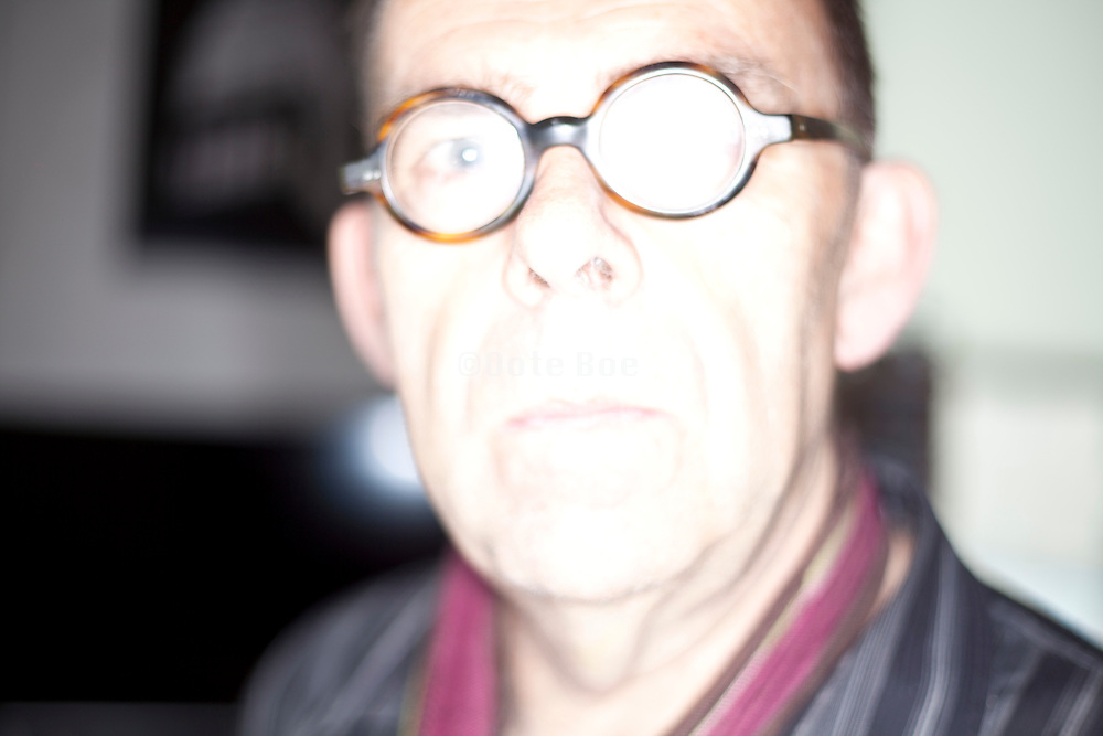 bright lighted portrait of adult man wearing glasses