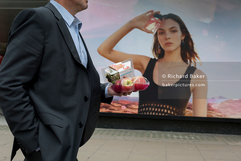 A man carries his salad and fruit lunch past a billboard ad featuring the face of a model advertising a perfume outside the retailer Debenhams on Oxford Street, on 16th April 2018, in London, England.