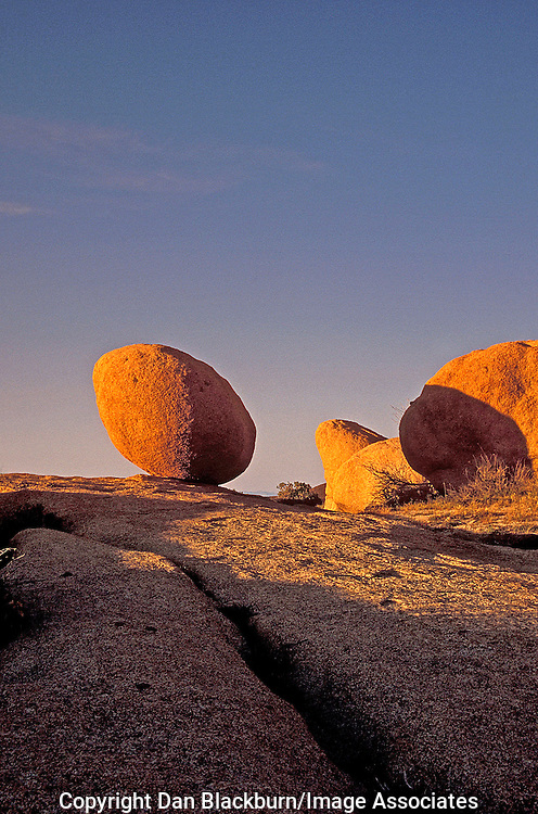 Balanced oval boulder is lit by the setting sun in Joshua Tree National Park, California.