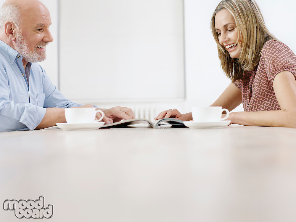 Couple sitting at table with coffee cups reading magazine together