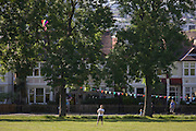 Man flies kite on a summer evening in front of Edwardian period homes in Ruskin Park, south London.