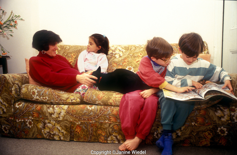 Pregnant mother on sofa relaxing with older children.